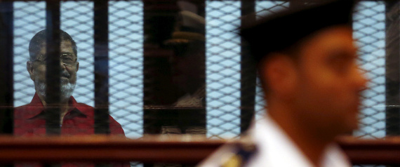 A police stands gurad in front of deposed President Mohamed Mursi which is seen behind bars at a court wearing the red uniform of a prisoner sentenced to death, during his court appearance with Muslim Brotherhood members on the outskirts of Cairo, Egypt, June 21, 2015. REUTERS/Amr Abdallah Dalsh/File Photo